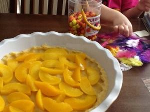 Kolmivuotias persikka-apuri asetteli hedelmäviipaleet vuokaan. Vaniljarahkaseos odottelee vuoroaan. Ja ei, helmet ja höyhenet eivät ole yllätystäyte, vaikka pinjataleivonnaiset houkuttelevatkin kokeilemaan!